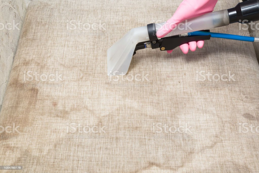 Dry cleaner\'s employee hand cleaning dirty sofa with professionally...
