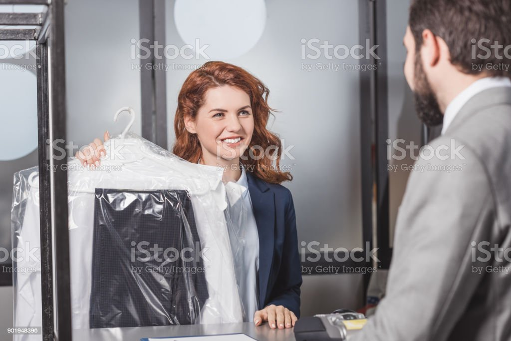 dry cleaning manageress holding bag of clothes for customer stock photo
