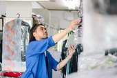 A dry cleaning shop owner is checking the clothes in his shop.