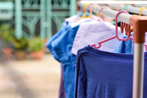 trockene kleidung und schule einheitliche hängen rack - mutterkleiderschrank stock-fotos und bilder