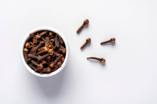 Dry clove spice Dry clove spice in a white bowl on a grey background, close-up, top view. clove spice stock pictures, royalty-free photos & images