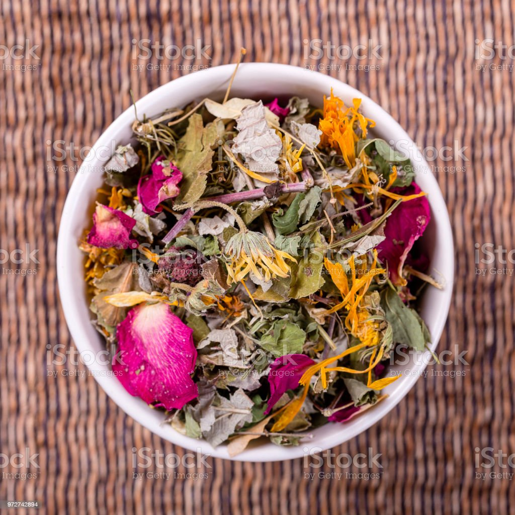 Different dry herbs and flowers for making healthy tea background in...