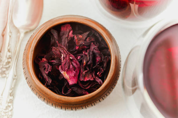 Dry flowers red hibiscus tea in a wooden  bowl close up on white background, view from the above stock photo