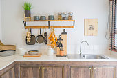 Arrangement of dry food products, spices and ceramics kitchen equipment hanging on country shelves in rustic home kitchen.