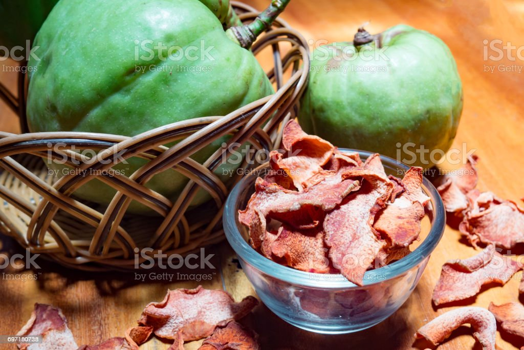 Dry garcinia in glass bowl with green Garcinia atroviridis fruit. Garcinia is healthy herb food that has high vitamin C and hydroxy citric acids (HCA) for diet. stock photo