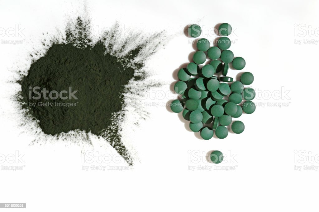 Dry green algae in powder and in tablets Isolated on white background. Algae Spirulina. Super food concept stock photo
