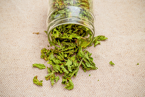 Dry green mint in a glass jar on a linen background. Healthy lifestyle