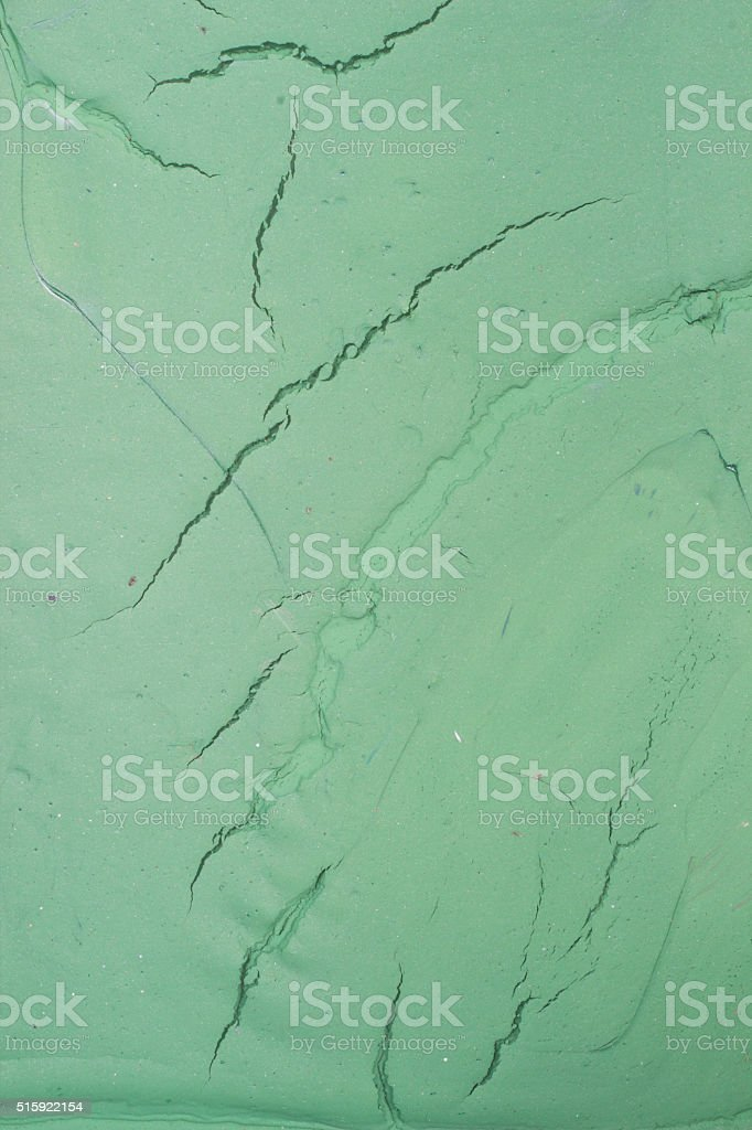 Dry green oil paint cracks and crevices texture for background stock photo