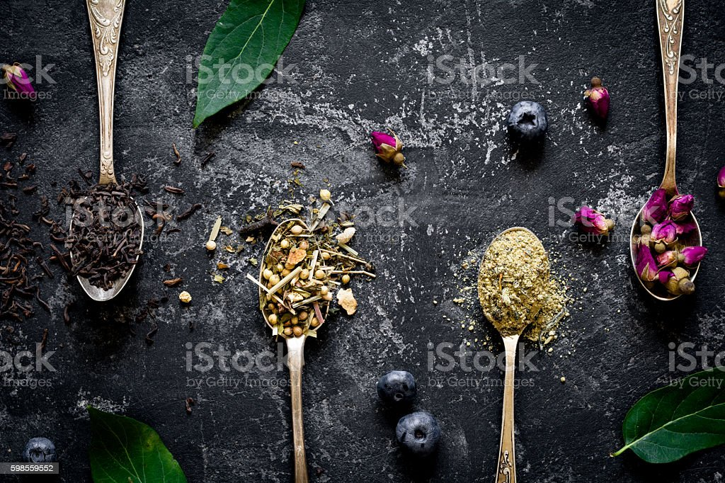 Dry herbal tea in tea spoons stock photo