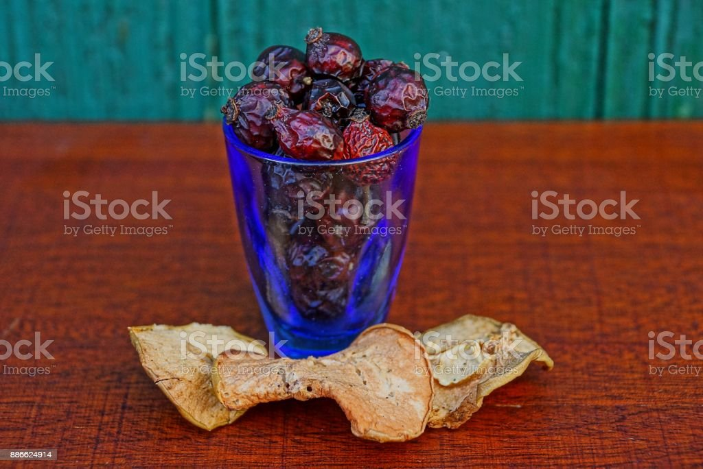 dry hips of a dogrose and pieces of a dry apple in a wine-glass and on a table stock photo