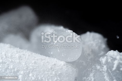 Dry ice cubes with vapor on black background.