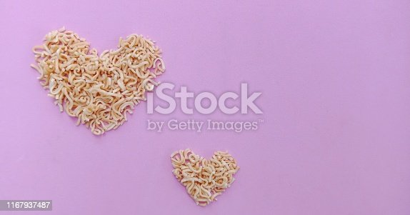 Dry instant noodles with heart shape on pink background.