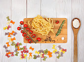 Dry Italian pasta fettuccini and farfalle with tomatoes, rosemary, mixture of peppers, spoon with flour and board on light wooden background. Top view with copy space
