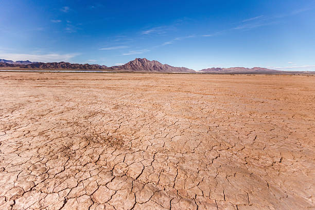 Dry lake bed in desert Cracked earth and deep blue skies, rocky mountains and alluvial fans in the panoramic image of the dry lake bed near Las Vegas, NV, California. Adobe RGB 1998 color profile. lake bed stock pictures, royalty-free photos & images