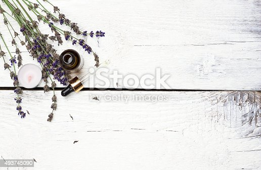 istock Dry lavender and oil  on a white wooden table 493745090