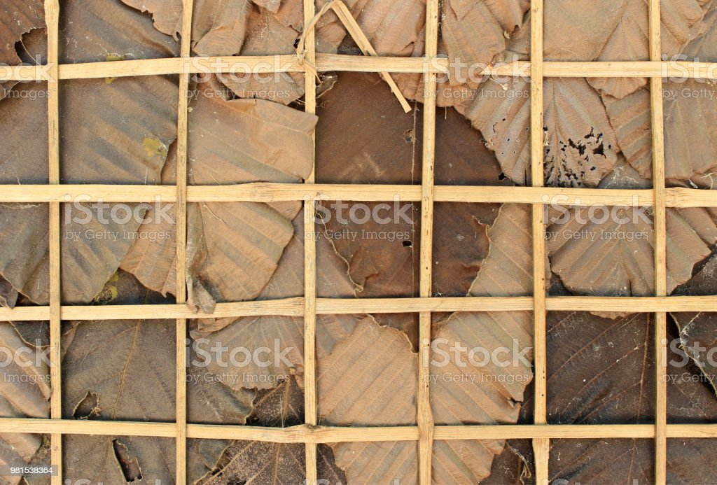 Dry leaves and weaved bamboo for background stock photo