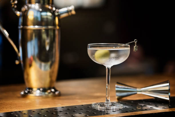 Dry Martini cocktail in vintage glass with jigger and shaker Ice cold Martini in vintage frosted glass with a green olive. A quintessential aperitif  synonym of luxury and good times. martini stock pictures, royalty-free photos & images