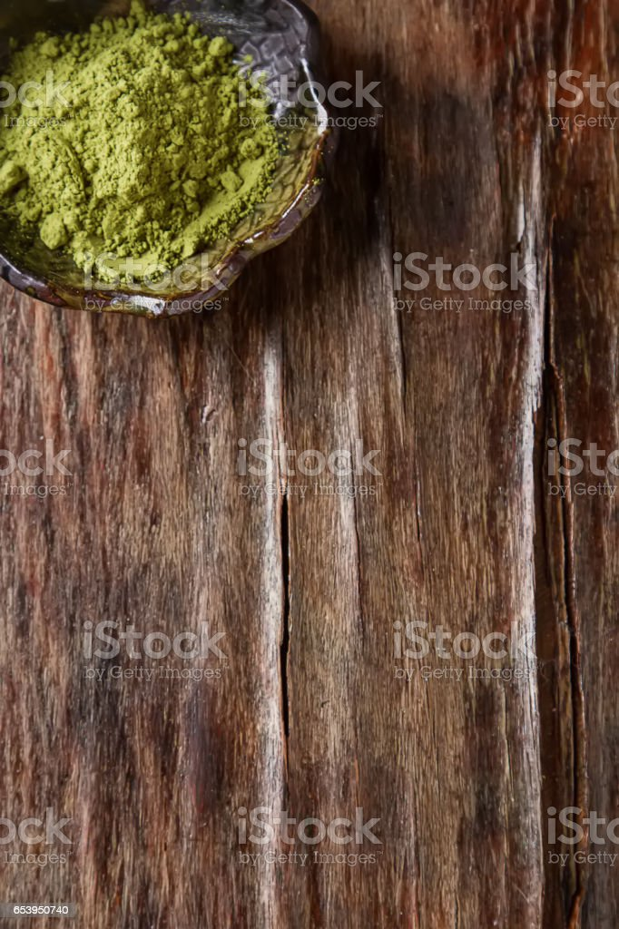 Dry Matcha tea in a small brown plate. Dark wood background. Top stock photo