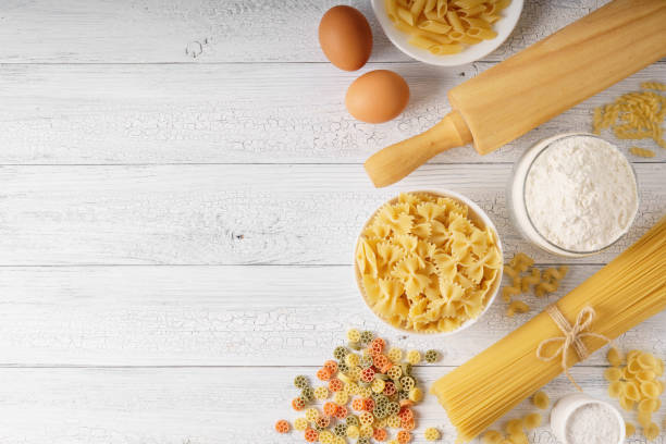 Dry mixed pasta, spaghetti and ingredients on a white rustic wooden background. Dry mixed pasta, spaghetti and ingredients on a white rustic wooden background with a copy spaсe top view shot. uncooked pasta stock pictures, royalty-free photos & images