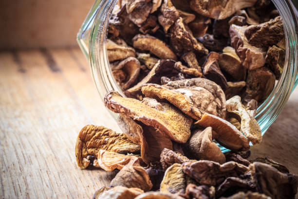 dry mushrooms in jar on wooden table. - dried food stock photos and pictures
