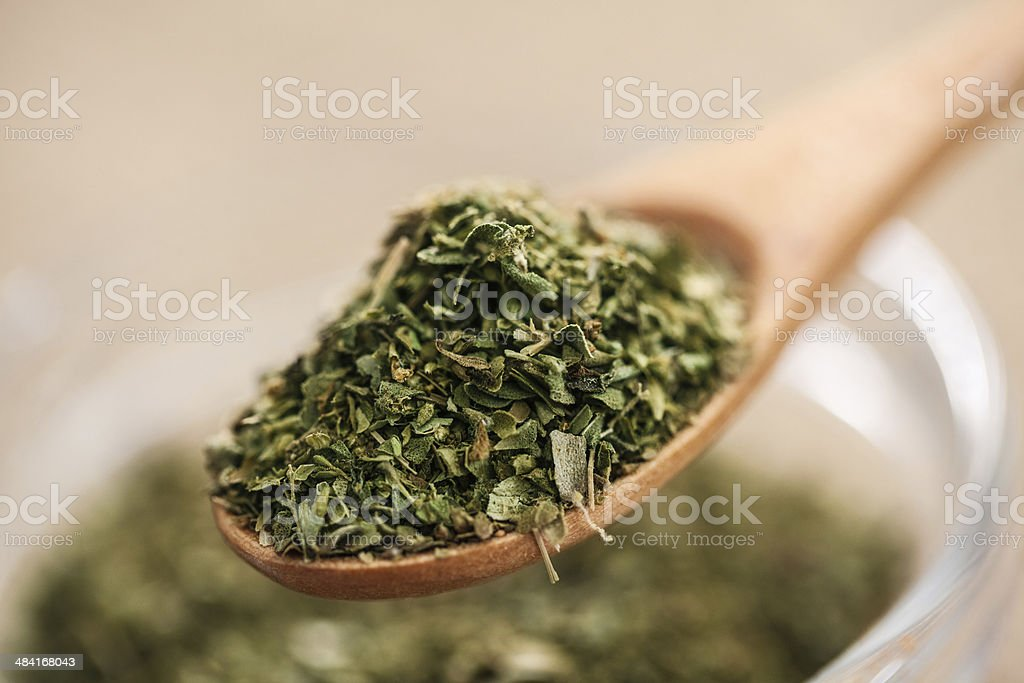 Dry Oregano in wood spoon - close up stock photo