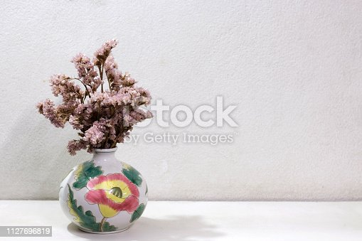 Dry pink Statice in beauty vase on white shelves with white cement wall background, home decor idea