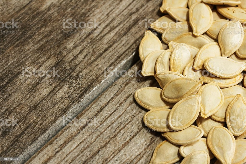 Dry Pumpkin seeds on a weathered wooden background stock photo