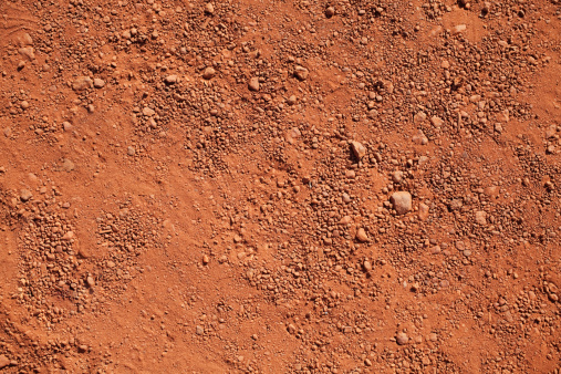 Texture of dry red clay with stones close-up