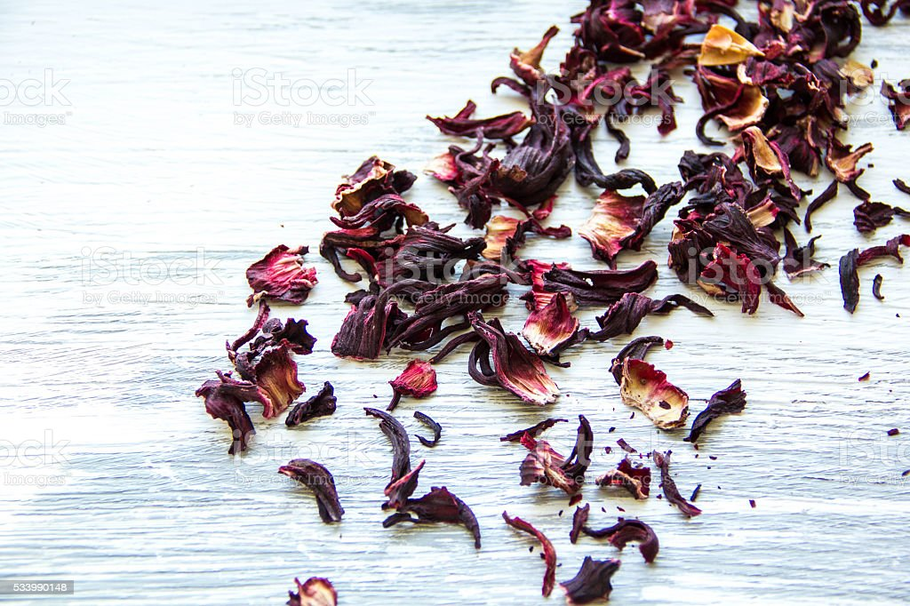 dry red tea leaves on wooden background stock photo