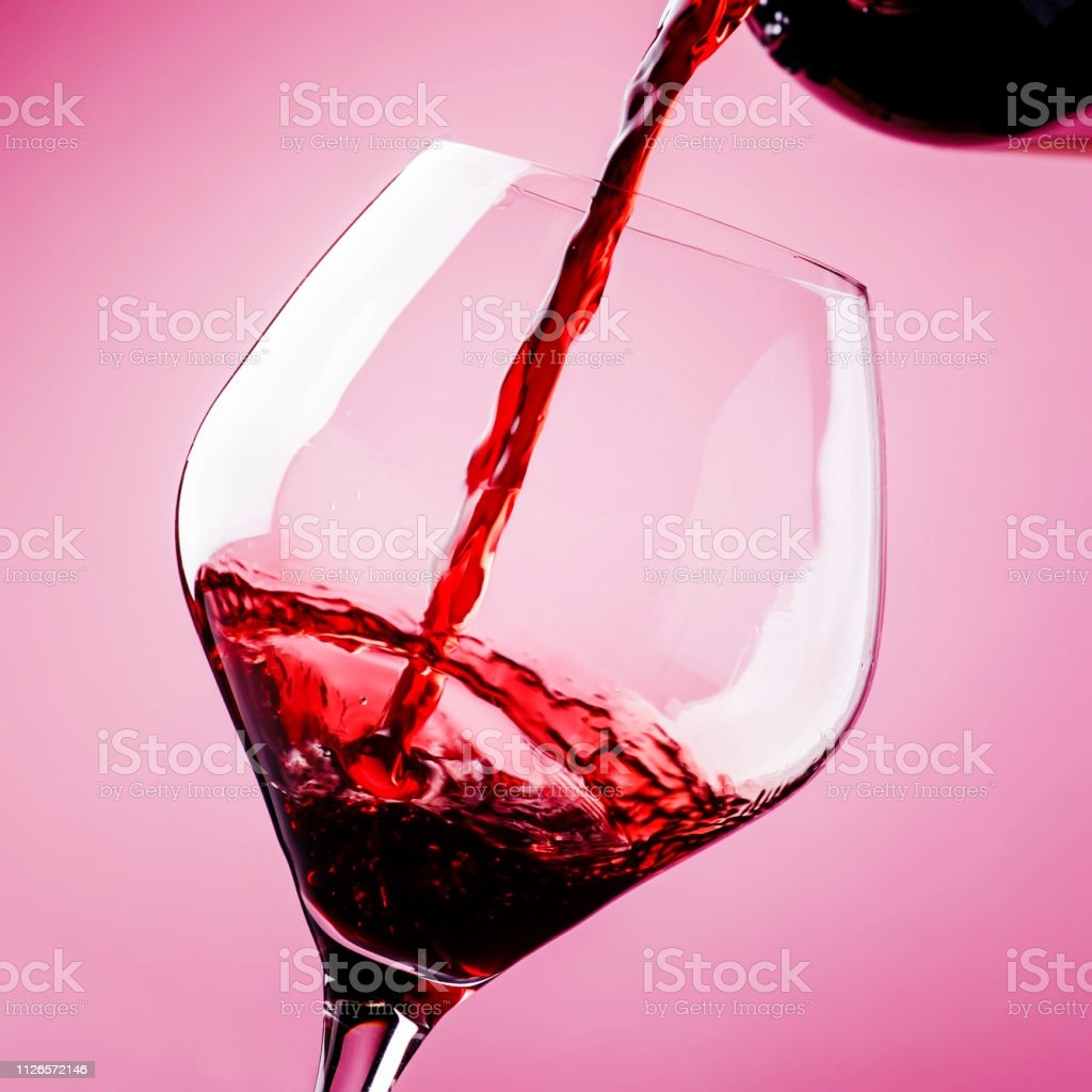 Dry red wine, splash in glass, pink background, defocused in motion image - foto stock