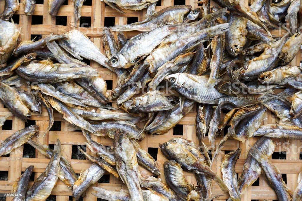 dry salty Minnow fish on bamboo basket stock photo