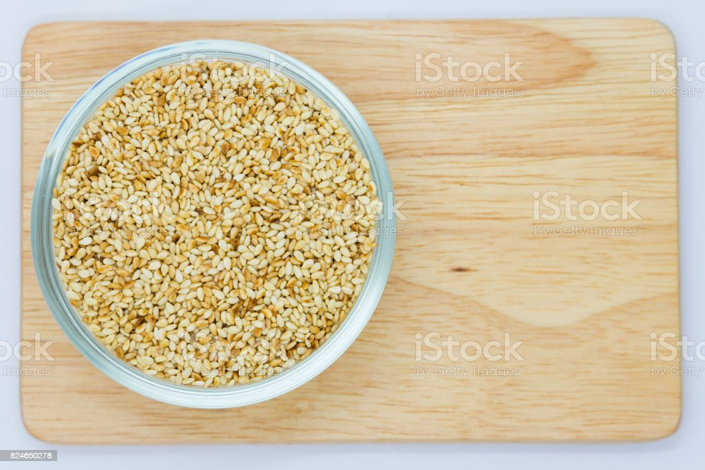Dry sesame seeds on wooden board stock photo