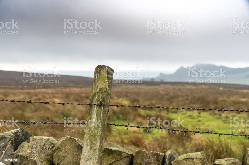 Dry Stone Wall and Barbed Wire in Rural Setting stock photo