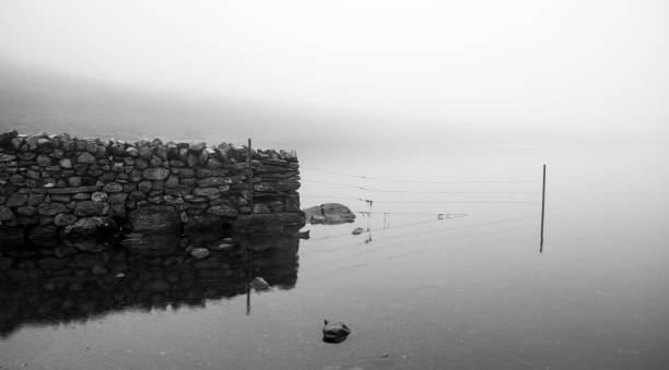 Dry stone wall reflected in mountain lake with low cloud stock photo