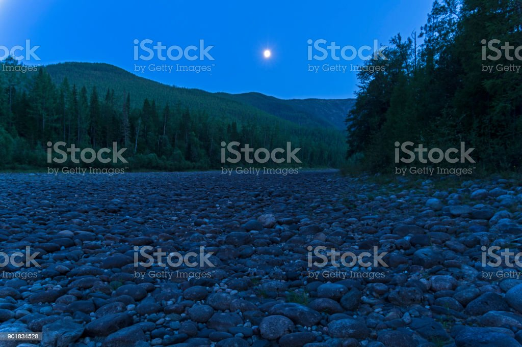 Dry stony river bed under the moonlight. stock photo