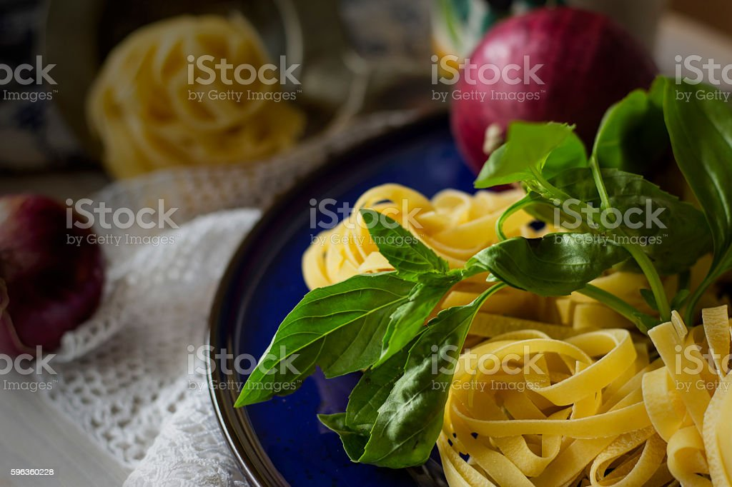 Dry tagliatelle pasta with basil royalty-free stock photo