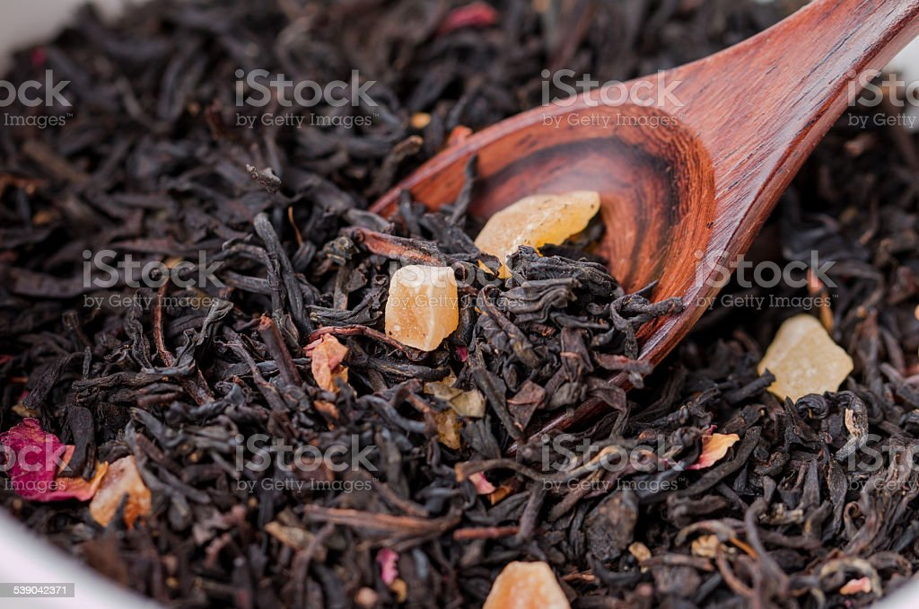 Dry tea leaves in wooden spoons stock photo