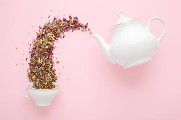 dry tea pouring from teapot into cup on pink - tea leaf stock photos and pictures