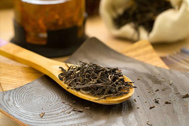 Dry tea puerh on a wooden spoon stock photo