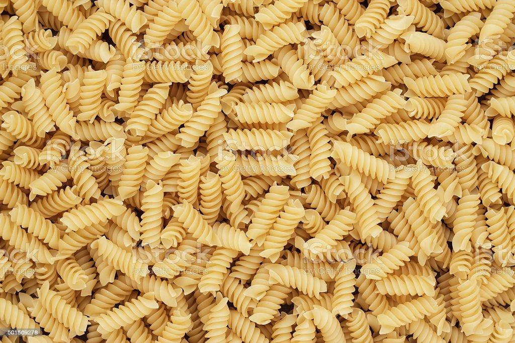dry uncooked rotini texture background stock photo
