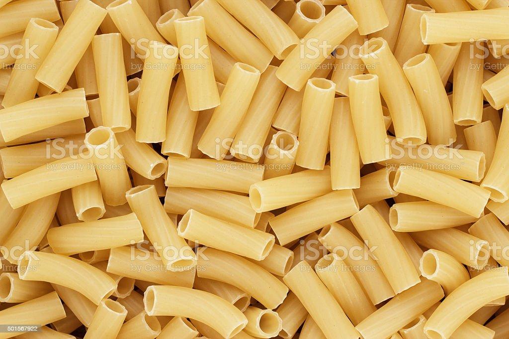 dry uncooked tortiglioni pasta texture background stock photo