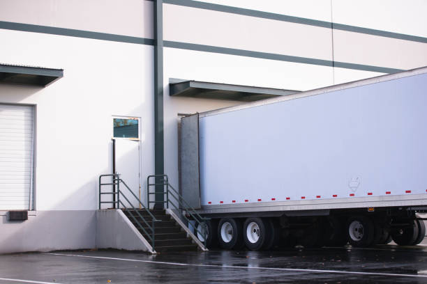 dry van semi trailer loading and unloading commercial cargo in warehouse dock - lorries unloading stock photos and pictures