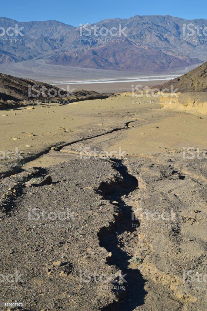 Dry wash between hills down into distant Salt Flats in desert...