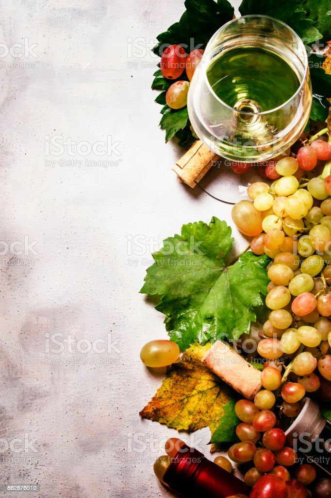 Dry white wine from chardonnay grapes, gray stone background, top view stock photo