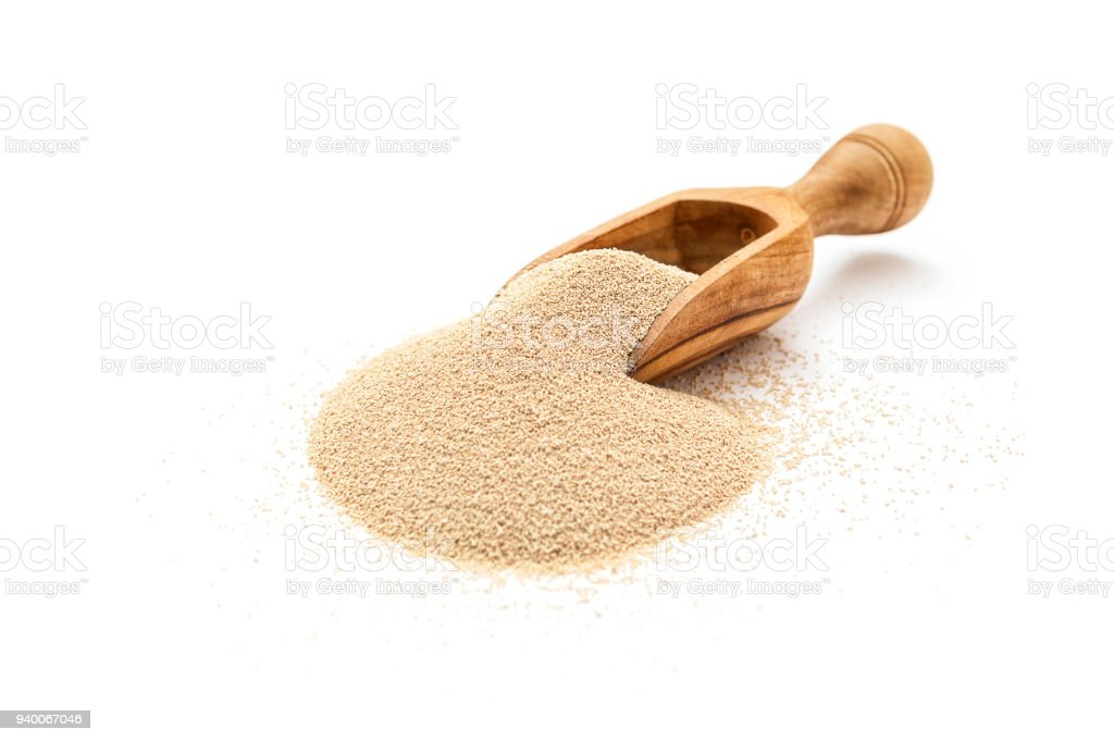 Dry yeast in wooden scoop stock photo
