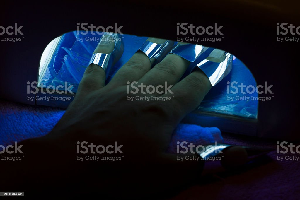 Drying female fingernail wax polish in ultraviolet light dryer stock photo