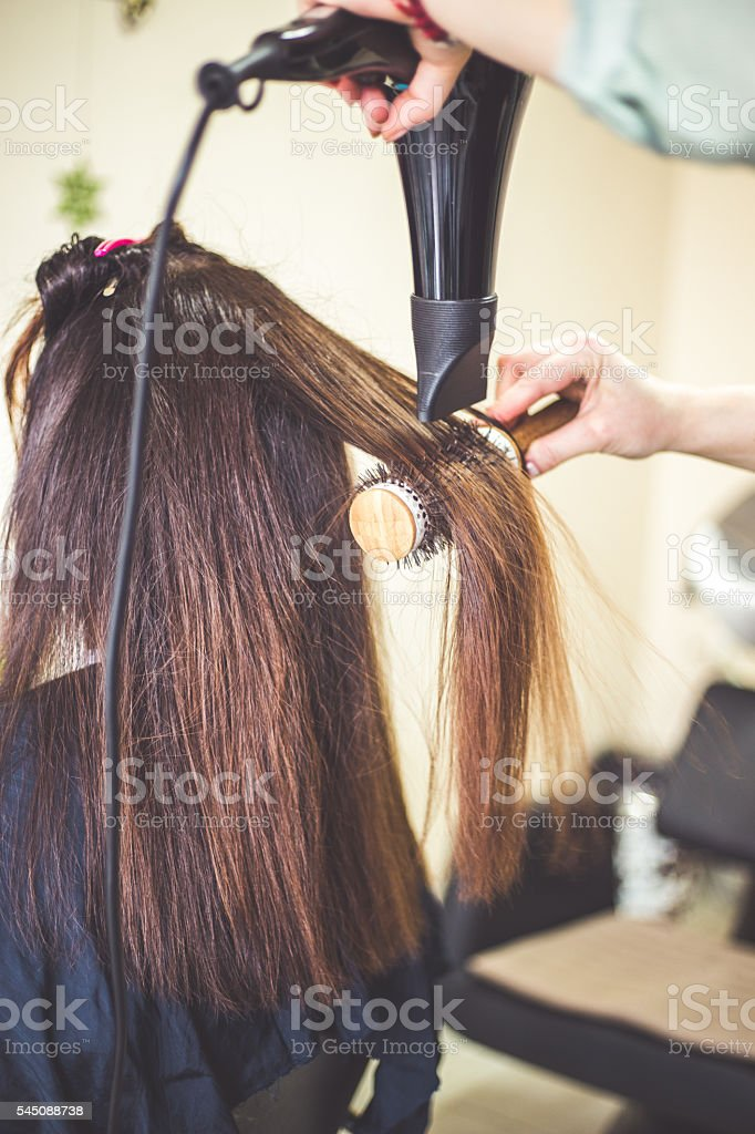 Drying Long Brown Hair With Hair Dryer And Round Brush Stock Photo