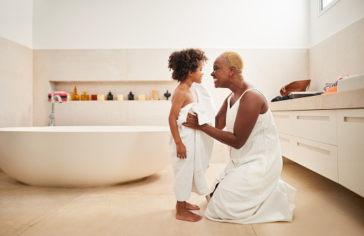 Shot of a woman drying her son with towel his bath in bathroom