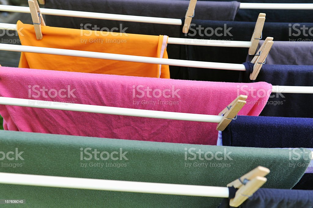 Drying rack with colored T-shirts and wooden clothespin royalty-free stock photo