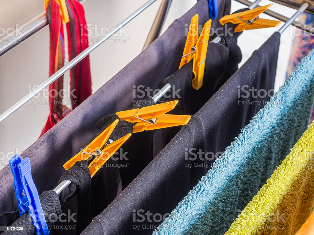 Drying rack with Colored T-shirts, Towels and Plastic Clothespin stock photo